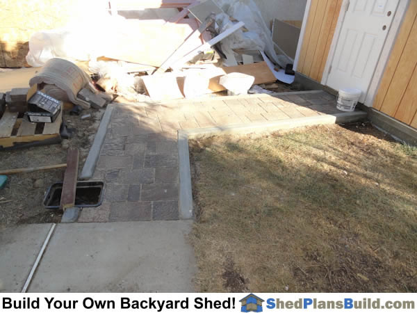 Pavers installed in front of backyard shed.