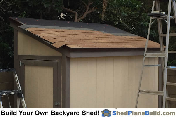 Installing asphalt roof shingles on storage shed.